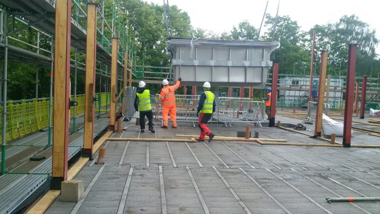 A hydrotherapy pool being craned into a pre-built hole in the ground
