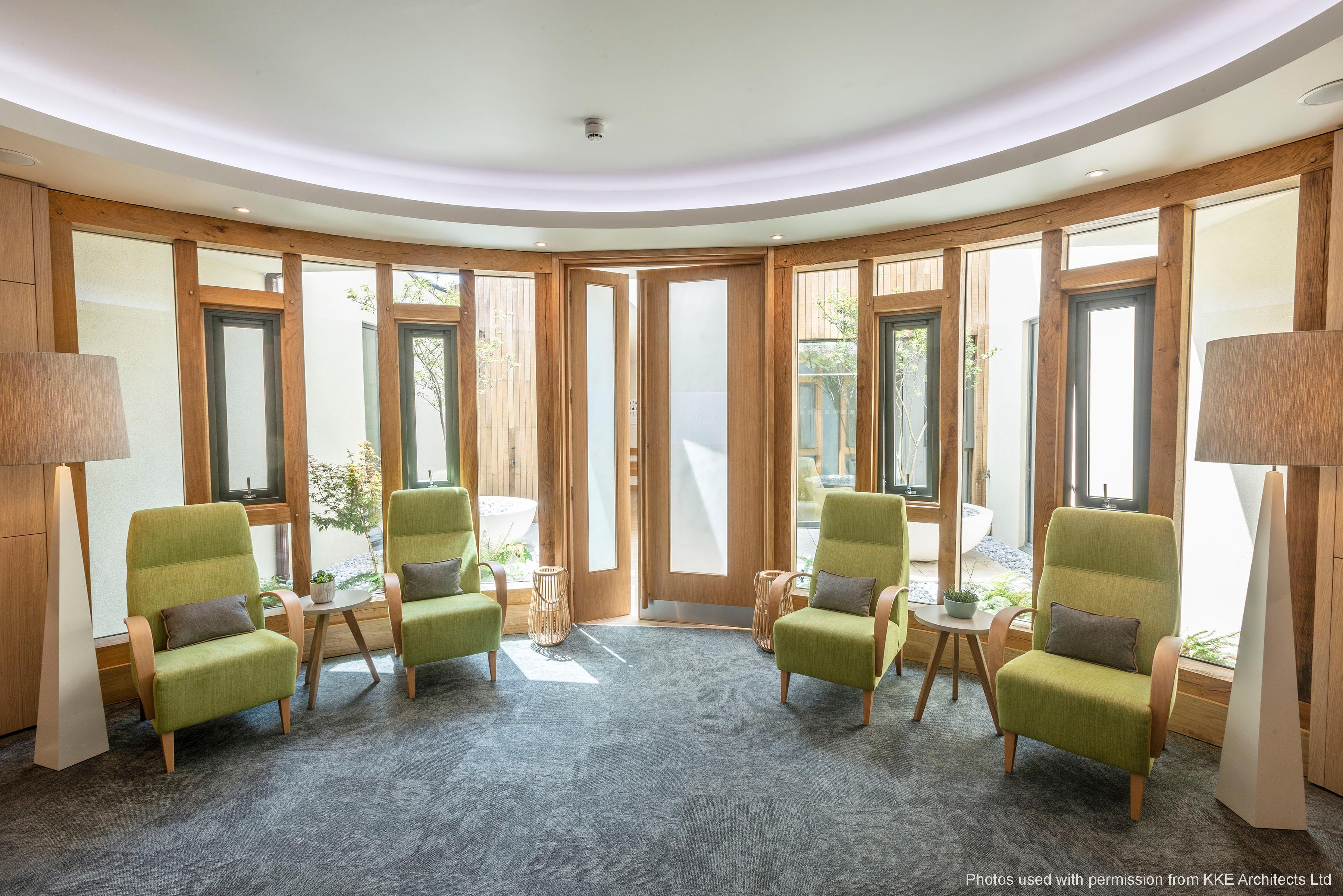 Some light green armchairs in a well-lit care home lounge.